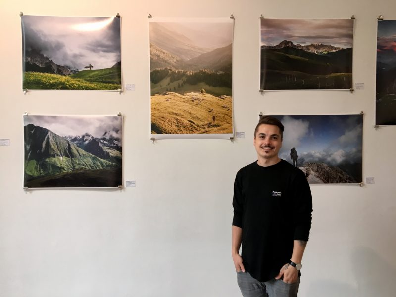 Photographer Bastian Schertel with his Landscape photography on the wall