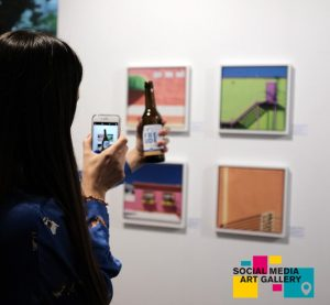 Person taking picture of beer in front of photography