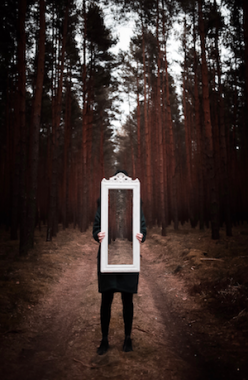 Person holding mirror in forest