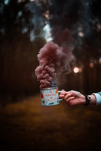 brown smoke out of a cup holding with hand