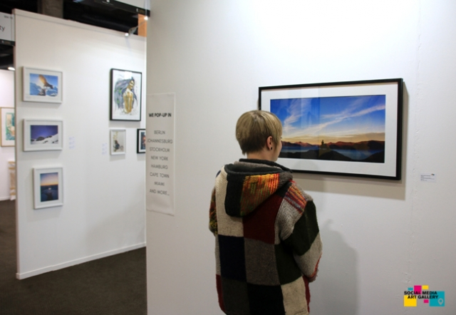 Visitor looking at photography by Bastian Schertel